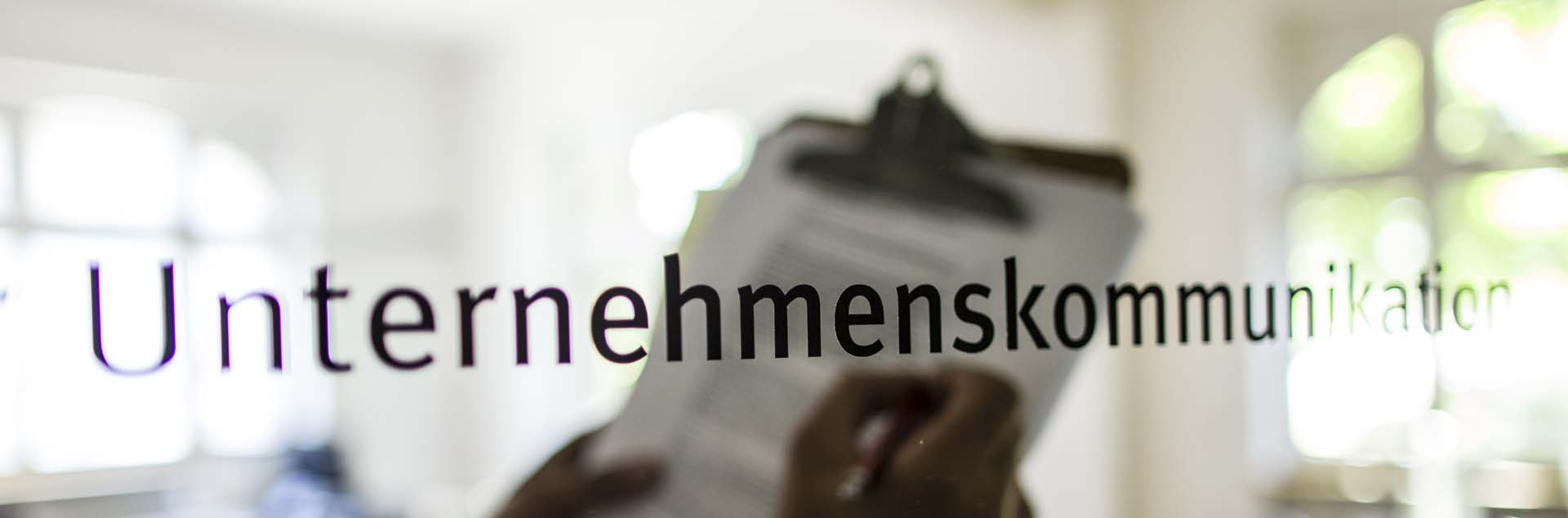 """Schriftzug """"Unternehmenskommunikation"""" auf einer Glastür"""