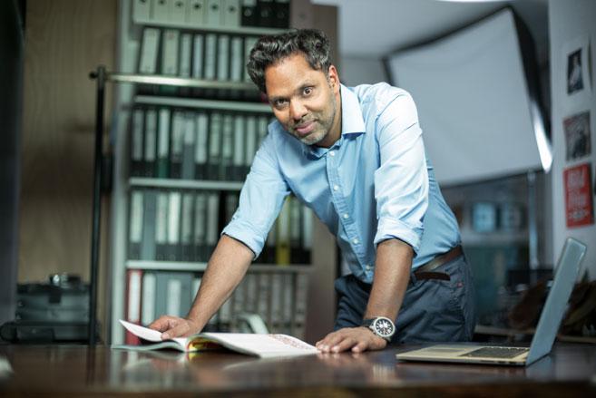 Murtaza Akbar, der Kommunikationsexperte und Keynote-Speaker steht vorgebeugt am Schreibtisch.